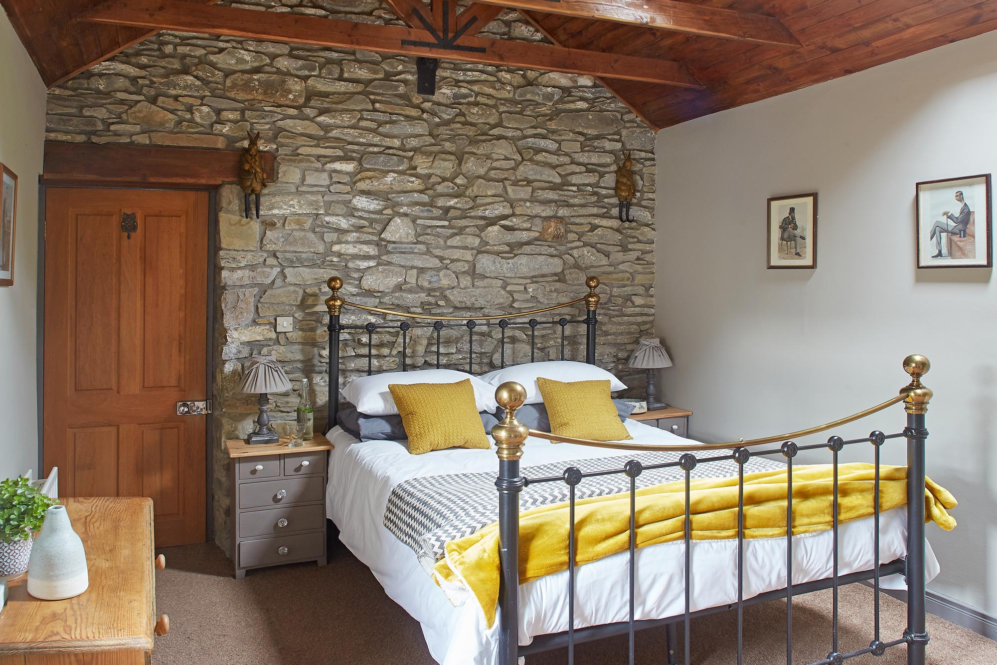 Converted barn guesthouse bedroom with stone walls and timbered ceiling